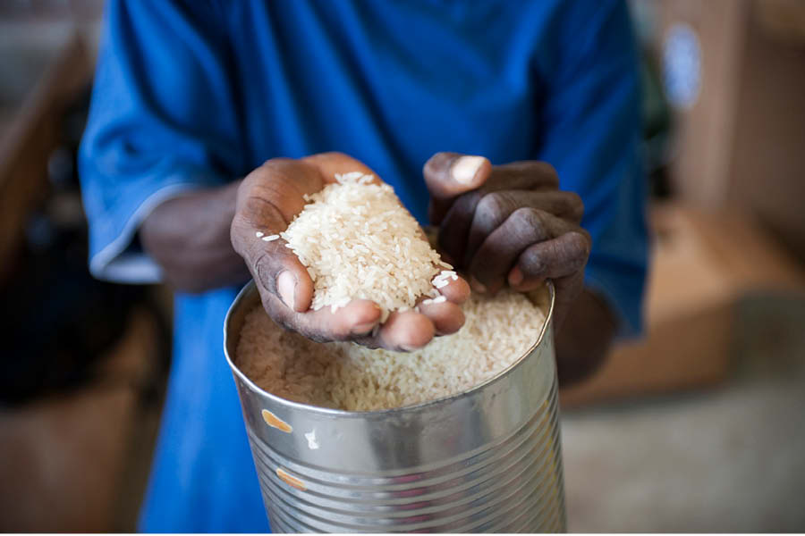 Haitian man holding uncooked rice
